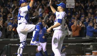 Chicago Cubs catcher Willson Contreras, left, and relief pitcher Mike Montgomery, right, celebrate after the Cubs defeated the Marlins 3-1 in a baseball game, Monday, June 5, 2017, in Chicago. (AP Photo/David Banks)