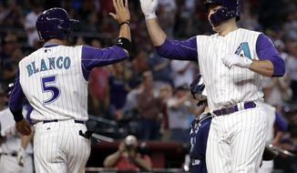 Arizona Diamondbacks' Chris Iannetta high fives teammate Gregor Blanco after hitting a two-run home run against the San Diego Padres during the fifth inning of a baseball game, Thursday, June 8, 2017, in Phoenix. (AP Photo/Matt York)