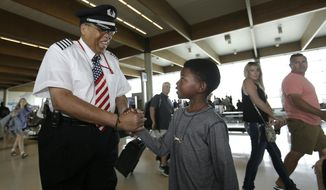 Cristopher Goods, 10, right, offers congratulations to Southwest Airlines captain Louis Freeman before Freeman piloted his last flight for the airline before his retirement in Dallas, Thursday, June 8, 2017. Freeman was the first African-Americansto become a chief pilot at a major U.S. airline and is retiring after a 36-year career that saw big changes in aviation. His most memorable flight carried the body of civil rights icon Rosa Parks. (AP Photo/LM Otero)