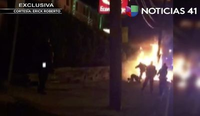 This image from video shot on June 4, 2017 shows a bystander being kicked by police officers, as he lies on the ground near flames, following an automobile chase that ended in a fiery crash, in Jersey City, N.Y. New Jersey authorities are investigating the video and a police spokesman said investigators have determined the person in the video, who also suffered burns, is not the person who was being pursued by police.  (Erick Roberto/Univision Channel 41 via AP)
