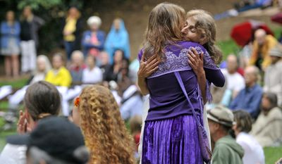 """Asha Deliverance, mother of Taliesin Namkai-Meche, is comforted by friends and family during a ceremony for a celebration of a life for Namkai-Meche at Lithia Park in Ashland, Ore., Wednesday, June 7, 2017. Jeremy Christian, accused of killing two men and wounding a third who tried to stop his anti-Muslim tirade against two teenagers on a Portland, Oregon, light-rail train, shouted he was """"not guilty"""" Wednesday during a courtroom outburst directed at one of the victims. (Jamie Lusch/The Medford Mail Tribune via AP)"""