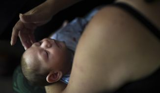 FILE - In this Dec. 16, 2016 file photo, Puerto Rico resident Michelle Flandez caresses her two-month-old son, Inti Perez, diagnosed with microcephaly linked to the mosquito-borne Zika virus, in Bayamon, Puerto Rico. According to a report released Thursday, June 8, 2017, on the impact of Zika virus in Puerto Rico and other U.S. territories, about 1 in 20 Zika-infected pregnant women had babies with birth defects. (AP Photo/Carlos Giusti)
