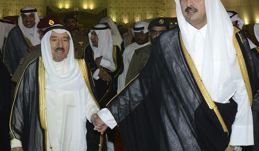"""In this Wednesday, June 7, 2017 photo released by Kuwait News Agency, KUNA, Kuwait's Emir Sheikh Sabah Al Ahmad Al Sabah, left, holds the hand of Qatar's Emir Sheikh Tamim bin Hamad Al Thani in Doha, Qatar. Kuwait's emir traveled to Qatar to help mediate an end to a crisis that's seen Arab nations cut ties to the energy-rich nation home to a major U.S. military base, though Emirati officials warned there was """"nothing to negotiate."""" (KUNA via AP)"""