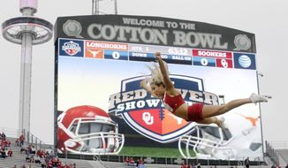 FILE - In this Oct. 11, 2014, file photo, an Oklahoma cheerleader flies in the air before an NCAA college football game between Texas and Oklahoma at the Cotton Bowl in Dallas. For the sake of the Big 12,  new Oklahoma coach Lincoln Riley and new Texas coach Tom Herman better live up to the hype. Following a season in which Big 12 football bottomed out, and with speculation about the long-term viability of the conference a constant talking point, its flagship programs are now both in transition.  (AP Photo/LM Otero, File)