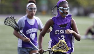 In this May 24, 2017, file photo Fadumo Adan, a lacrosse player at Deering High School, wears a sports hijab provided by the school during practice in Portland, Maine. Deering High School is providing sport hijabs with the goal of making Muslim girls comfortable and boosting their participation in sports. Tennis co-captains Liva Pierce and Anaise Manikunda solicited private donations to avoid criticism for using taxpayer funds on religious apparel, and ended up with enough to outfit all teams, including lacrosse, soccer, volleyball, softball, field hockey and track. (AP Photo/Robert F. Bukaty)