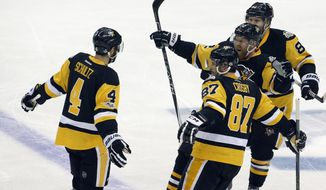 Pittsburgh Penguins' Sidney Crosby (87), Patric Hornqvist, second from right, and Phil Kessel, right, rush to celebrate a goal by Justin Schultz, left, during the first period in Game 5 of the NHL hockey Stanley Cup Final against the Nashville Predators, Thursday, June 8, 2017, in Pittsburgh. (AP Photo/Gene J. Puskar)