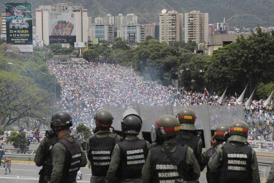 FILE - In this May 3, 2017 file photo, Bolivarian National Guards stand on a highway overlooking an anti-government march trying to make its way to the National Assembly in Caracas, Venezuela. The military has helped hold up President Nicolas Maduro's administration for more than a decade, and despite the outward loyalty of top officers, cracks are beginning to appear. (AP Photo/Fernando Llano, File)