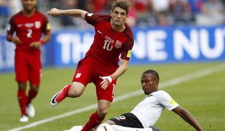 U.S. midfielder Christian Pulisic, front, jumps over Trinidad & Tobago forward Kenwyne Jones while pursuing the ball during the first half of a World Cup soccer qualifying match Thursday, June 8, 2017, in Commerce City, Colo. (AP Photo/David Zalubowski)
