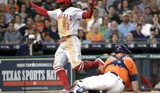 Los Angeles Angels' Cameron Maybin (9) avoids Houston Astros catcher Brian McCann (16) as he scores during the sixth inning of a baseball game Friday, June 9, 2017, in Houston. (AP Photo/David J. Phillip)