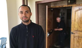 In this June 1, 2017, photo, Drew Williams, a member of the Eugene Islamic Center, poses for a portrait outside the building in Eugene, Ore., as locksmith Jim King upgrades the locks on the front doors. Williams said members of the mosque have been rattled by an incident in which a man showed up and allegedly threatened to kill worshippers, but that the community has shown concern and support. (AP Photo/Andrew Selsky)