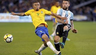 Nicolas Otamendi of Argentina, right, kicks the ball past Gabriel Jesus of Brazil during their friendly soccer international at the Melbourne Cricket Ground in Melbourne, Australia, Friday, June 9, 2017. (Joe Castro/AAP Image via AP)