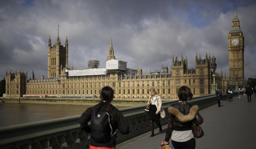 People cross Westminster Bridge in front of the Houses of Parliament the day after Britain's national elections in London, Friday, June 9, 2017 in this file photo. (AP Photo/Markus Schreiber)