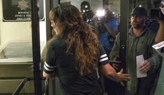 Chauna Thompson, foreground, and her husband, Terry Thompson, right, turn themselves in to the Harris County Sheriff's Office on Thursday, June 8, 2017, in Houston. Thompson, a Harris County Sheriff's deputy, and her husband were indicted on murder charges in the death of a man they restrained during a late night confrontation outside of a restaurant while she was off duty. (Brett Coomer/Houston Chronicle via AP)