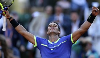 Spain's Rafael Nadal raises his arms in victory after defeating Austria's Dominic Thiem during their semifinal match of the French Open tennis tournament at the Roland Garros stadium, Friday, June 9, 2017 in Paris. Nadal won 6-3, 6-4, 6-0. (AP Photo/David Vincent)