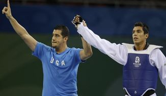 File- This Aug. 22, 2008, file photo shows Steven Lopez of the US, right, celebrating with his brother and coach Jean after defeating Azerbaijan's Rashad Ahmadov in a bronze medal match for the men's taekwondo -80 kilogram class at the Beijing 2008 Olympics in Beijing. USA Today reported Friday, June 9, 2017, that USA Taekwondo began investigating claims against Steven and Jean Lopez more than two years ago after multiple women said the brothers sexually assaulted them. (AP Photo/Matt Dunham, File)
