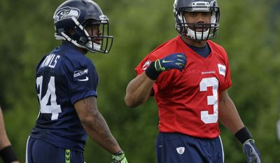 Seattle Seahawks quarterback Russell Wilson (3) stands with running back Thomas Rawls, left, during NFL football practice, Friday, June 9, 2017, in Renton, Wash. (AP Photo/Ted S. Warren)