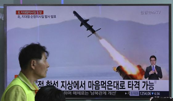 """A man passes by a TV news program showing a photo published in North Korea's Rodong Sinmun newspaper of North Korea's new type of cruise missile launch, at Seoul Railway station in Seoul, South Korea, Friday, June 9, 2017. North Korea said Friday it has tested a new type of cruise missile that could strike U.S. and South Korean warships """"at will"""" if it is attacked, in an apparent reference to the projectiles detected by Seoul when they were launched a day earlier. The signs read """"Can hit on the ground."""" (AP Photo/Ahn Young-joon) ** FILE **"""