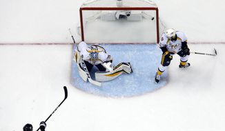 Pittsburgh Penguins' Bryan Rust (17) gets a shot behind Nashville Predators goalie Pekka Rinne (35) with Colton Sissons (10) defending for a goal during the first period of Game 5 of the NHL Stanley Cup Final, Thursday, June 8, 2017, in Pittsburgh. (AP Photo/Gene J. Puskar)