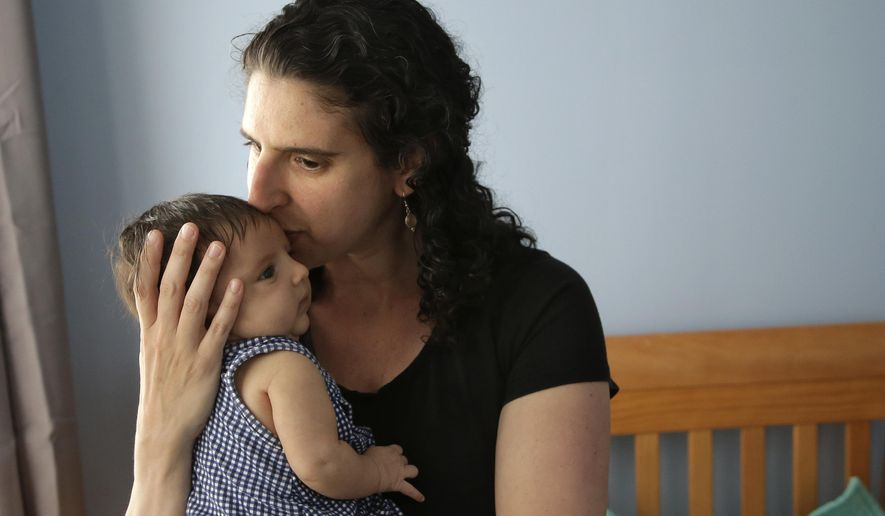 In this Thursday, June 1, 2017 photo Elena Tenenbaum kisses her eight-week-old baby Zoe while standing for a photograph at their home in Providence, R.I. Tenenbaum, a clinical psychology researcher, had her second daughter in April of 2017, and has been able to use Rhode Island's paid family leave program, which started in 2014 and covers four weeks of partial pay. (AP Photo/Steven Senne)