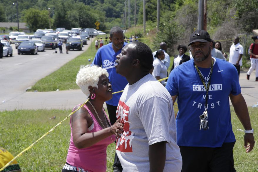 Tulsa resident Angie Pitts, left, tries to calm down others as law enforcement officials investigate near 46th Street North and Martin Luther King Jr. Boulevard, Friday, June 9, 2017 in Tulsa, Okla. Law officers in Tulsa fatally shot a man while trying to pick him up for a mental health issue, triggering a street protest and a corresponding show of force by police in riot gear. (Cory Young/Tulsa World via AP)