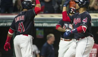 Cleveland Indians' Carlos Santana (41) greets Edwin Encarnacion, after Encarnacion's two-run home run off Chicago White Sox starting pitcher Miguel Gonzalez during the fifth inning of a baseball game in Cleveland, Friday, June 9, 2017. (AP Photo/Phil Long)