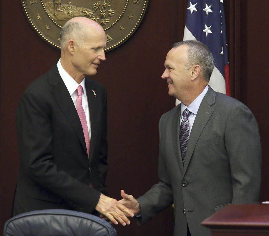 Gov. Rick Scott, left, shakes hands with house speaker Richard Corcoran, R-Land O'Lakes, as the house takes up legislation to repair the Herbert Hoover dike around Lake Okeechobee during session, Friday, June 9, 2017, in Tallahassee, Fla. (AP Photo/Steve Cannon)
