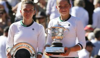 Latvia's Jelena Ostapenko, right, and Romania's Simona Halep hold their trophy after their final match of the French Open tennis tournament at the Roland Garros stadium, Saturday, June 10, 2017 in Paris. Ostapenko won 4-6, 6-4, 6-3. (AP Photo/David Vincent)
