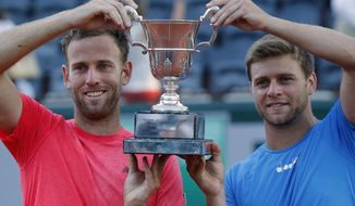 Ryan Harrison of the U.S. and Michael Venus of New Zealand, left, hold the trophy after winning the men's doubles final match of the French Open tennis tournament against Santiago Gonzalez of Mexico and Donald Young of the U.S. in three sets 7-6 (7-5), 6-7 (4-7), 6-3, at the Roland Garros stadium, in Paris, France, Saturday, June 10, 2017. (AP Photo/Michel Euler)