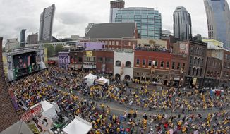 FILE -- In this June 5, 2017 file photo, people watch a pre-game concert as they wait to watch the broadcast of Game 4 of the NHL hockey Stanley Cup Finals between the Nashville Predators and the Pittsburgh Penguins on Broadway in Nashville, Tenn. The Predators host Game 6 on Sunday evening at the same time that the annual CMA Music Festival holds its concert headlined by Keith Urban and Brad Paisley in nearby Nissan Stadium, the home of the Tennessee Titans. The honky-tonk lined blocks in between the two venues are expected to packed with even more fans, and city officials expect a total of 100,000 people to throng the downtown streets. (AP Photo/Mark Humphrey, File)