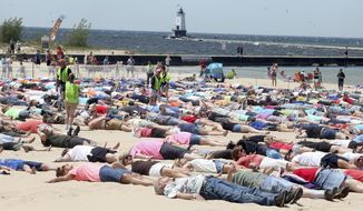 People take part in an attempt to break the Guinness Book record for simultaneous sand angels on Saturday, June 10, 2017 in Ludinton, Mich.  Around 1,387 people angelically assembled on a Lake Michigan beachfront in Ludington on Saturday and worked their magic for 30 seconds. That far surpasses the roughly 350 who made sand angels for 15 seconds two years ago in Pembrokeshire, United Kingdom.  (Jeff Kiessel/Ludington Daily News via AP)