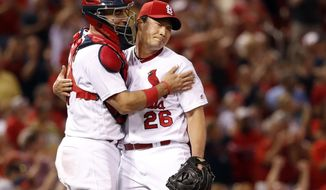 St. Louis Cardinals relief pitcher Seung-Hwan Oh (26) and teammate Eric Fryer celebrate following a baseball game against the Philadelphia Phillies on Friday, June 9, 2017, in St. Louis. The Cardinals won 3-2. (AP Photo/Jeff Roberson)
