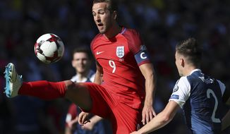 England's Harry Kane, left, view for the ball next to Scotland's Charlie Tierney during the World Cup Group F qualifying soccer match between Scotland and England at Hampden Park, Glasgow, Scotland, Saturday, June 10, 2017. (AP Photo/Scott Heppell)