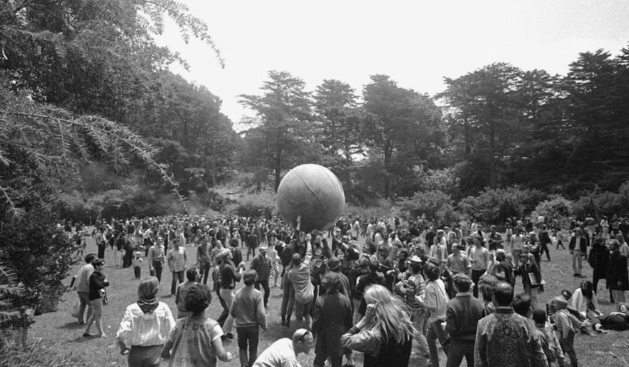"ADVANCE FOR USE TUESDAY, JUNE 13, 2017 AND THEREAFTER-FILE - In this June 21, 1967 file photo, people keep a large ball, painted to represent a world globe, in the air during a gathering at Golden Gate Park in San Francisco, to celebrate the summer solstice on June 21, day one of ""Summer of Love."" City officials have rejected a permit for a planned free concert intended to mark the 50th anniversary of the famed Summer of Love in Golden Gate Park that had been planned for June 2017. (AP Photo/File)"