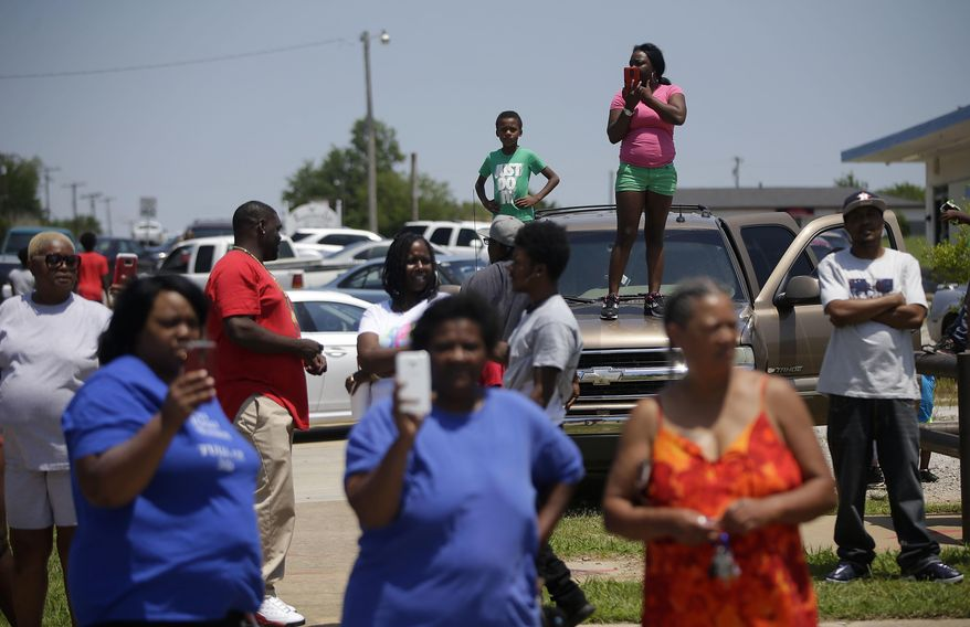 A crowd gathers after a man was fatally shot, Friday, June 9, 2017 in Tulsa, Okla. Law officers in Tulsa fatally shot a man while trying to pick him up for a mental health issue, triggering a street protest and a corresponding show of force by police in riot gear. (Cory Young/Tulsa World via AP)