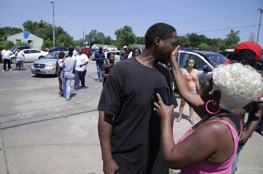 Tulsa resident Angie Pitts, right, tries to calm down others as law enforcement officials investigate near 46th Street North and Martin Luther King Jr. Boulevard, Friday, June 9, 2017 in Tulsa, Okla. Law officers in Tulsa fatally shot a man while trying to pick him up for a mental health issue, triggering a street protest and a corresponding show of force by police in riot gear. (Cory Young/Tulsa World via AP)