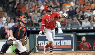 Los Angeles Angels' Eric Young Jr. (8) watches his three-run home run along with Houston Astros catcher Evan Gattis during the fifth inning of a baseball game, Sunday, June 11, 2017, in Houston. (AP Photo/David J. Phillip)