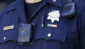 In this May 13, 2017 photo, San Francisco Police officer Joe Juarez wears a body camera while patrolling outside of AT&T Park before a baseball game between the San Francisco Giants and the Cincinnati Reds in San Francisco. (AP Photo/Jeff Chiu)