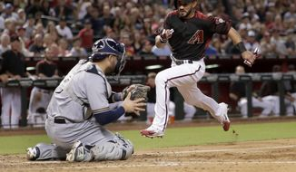 Arizona Diamondbacks Reymond Fuentes scores on a base hit by Zack Godley as Milwaukee Brewers catcher Manny Pina (9) kneels at the plate during the fifth inning of a baseball game, Saturday, June 10, 2017, in Phoenix. (AP Photo/Matt York)