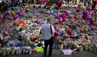 FILE- In this Friday, May 26 2017 file photo, a man stands next to flowers for the victims of Monday's bombing at St Ann's Square in central Manchester, England, Friday, May 26 2017. British police say everyone arrested over the Manchester concert bombing has been released without charge, but detectives are still not sure whether the attacker had accomplices. (AP Photo/Emilio Morenatti, File)