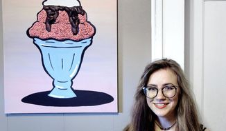 "In this May 11, 2017 photo, Vanessa Cox, a graduate of Hastings College, stands with her senior thesis ""The Gingerbug House"" in her Hastings, Neb., home. Cox made the piece at the college to explore the concerns of decreasing food sources. Cox used cockroaches and meal worms as part of her mixed media artwork. (Zach Mayhew/The Independent via AP)"