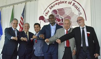International Boxing Hall of Fame Class of 2017 inductees, from left, Steve Farhood, Barry Tompkins, Marco Antonio Barrera, Evander Holyfield, Jerry Roth and Johnny Lewis display their rings following the induction ceremony in Canastota, N.Y., Sunday, June 11, 2017. (Kyle Mennig/Oneida Daily Dispatch via AP)