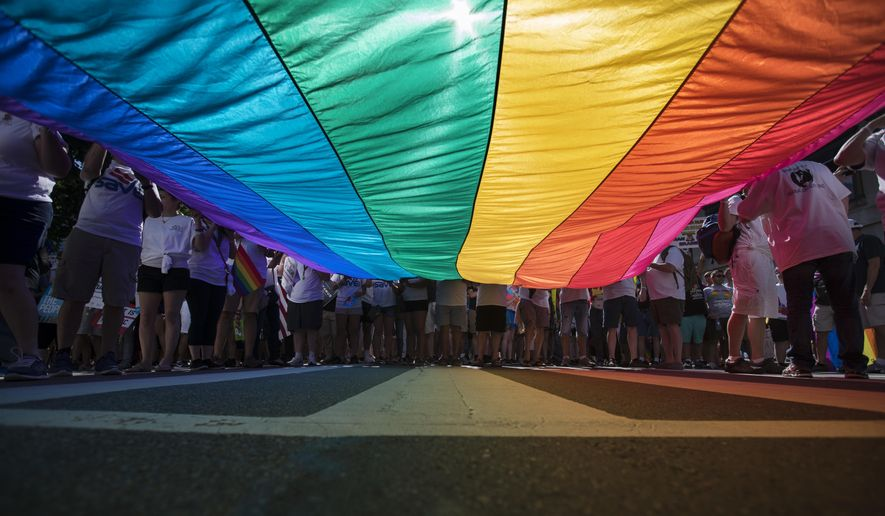 Marchers unfurl a huge rainbow flag as they prepare to march in the Equality March for Unity and Pride in Washington, Sunday, June 11, 2017. (AP Photo/Carolyn Kaster)