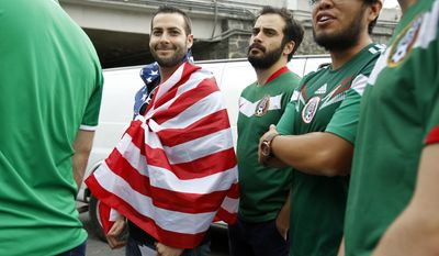 A man with the wrapped on the U.S. flag arrives to the stadium before the World Cup soccer qualifying match between Mexico and the U.S. at Azteca Stadium in Mexico City, Sunday, June 11, 2017.(AP Photo/Rebecca Blackwell)