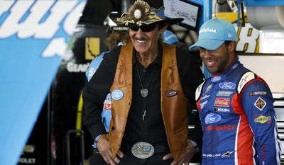 Driver Darrell Wallace Jr., right, and team owner Richard Petty laugh in the garage during practice for Sunday's NASCAR Cup Series Pocono 400 auto race, Friday, June 9, 2017, in Long Pond, Pa. (AP Photo/Matt Slocum)