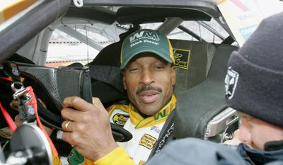 FILE - In the March 20, 2006, file photo, NASCAR driver Bill Lester puts on his head and neck restraint in his car as he gets ready for a rain-delayed start of the NASCAR Golden Corral 500 auto race at Atlanta Motor Speedway, in Hampton, Ga. On Sunday, June 11, 2017, Darrell Wallace Jr. became just the eighth black driver to race in NASCAR's top Cup series when he started at Pocono Raceway.  Lester was rooting for Wallace on Sunday. Lester made two starts in 2006 and was the last black driver to make a Cup start. Lester met Wallace at a Truck race in Kansas a few years ago and had followed his progression through NASCAR. (AP Photo/Ric Feld, File)