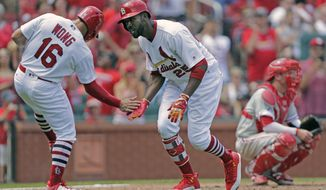 St. Louis Cardinals' Dexter Fowler (25) celebrates with teammate Kolten Wong (16) after hitting a three-run home run, as Philadelphia Phillies catcher Andrew Knapp looks on, in the fifth inning of a baseball game, Sunday, June 11, 2017, in St. Louis. (AP Photo/Tom Gannam)