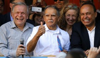 In this May 18, 2017, file photo, Puerto Rican nationalist Oscar Lopez Rivera, center, reacts to the crowd as his brother Jose, left, and U.S. Rep Luis Gutierrez, D-Ill., join him at a gathering in his honor in Chicago's Humboldt Park neighborhood. New York City's annual Puerto Rican Day parade will take place under a cloud of controversy this year because of a decision by organizers to honor Lopez Rivera, who spent decades in prison because of his involvement with the terrorist group FALN. (AP Photo/Charles Rex Arbogast, File)