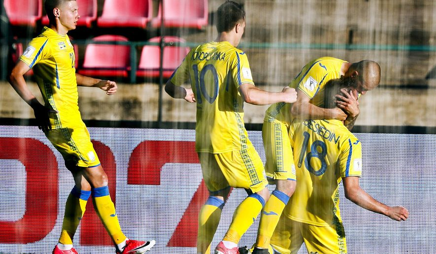 Artem Besedin of Ukraine, right, celebrates with his team mates after scoring the winning goal 1-2 during the World Cup qualifying Group I soccer match between Finland and Ukraine in Tampere, Finland, Sunday, June 11, 2017.  (Mika Kanerva/Lehtikuva via AP)
