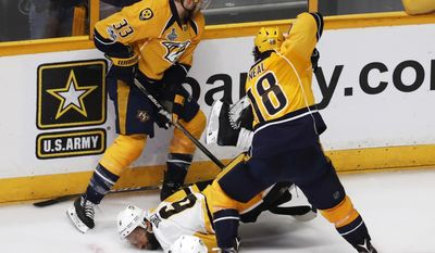 Pittsburgh Penguins' Trevor Daley (6) falls as he battles for the puck against Nashville Predators' Colin Wilson (33) and James Neal (18) during the third period of Game 6 of the NHL hockey Stanley Cup Final, Sunday, June 11, 2017, in Nashville, Tenn. (AP Photo/Jeff Roberson)