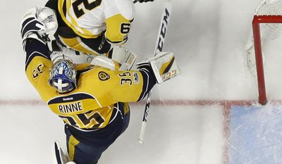 Pittsburgh Penguins' Carl Hagelin (62), of Sweden, battles for the puck against Nashville Predators goalie Pekka Rinne (35), of Finland, during the third period of Game 6 of the NHL hockey Stanley Cup Final, Sunday, June 11, 2017, in Nashville, Tenn. (AP Photo/Mark Humphrey)